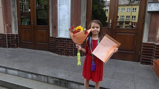 Sárinka se svým vysvědčením před školou.