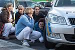 4 z 9 - Zaměstnanci nemocnice se skrývají za policejními vozidly poblíž místa střelby ve Fakultní nemocnici v Ostravě, 10. prosince 2019.
