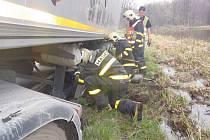 Hasiči vyprošťují kamion, který uvízl v rozměklé půdě vedle silnice.