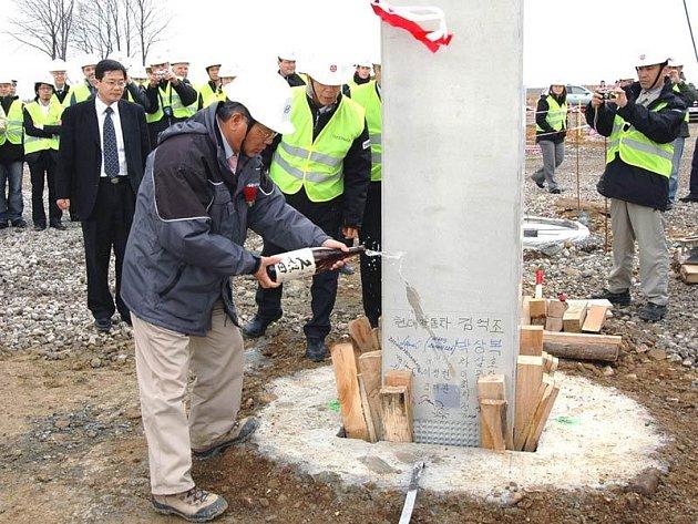 Šéf české pobočky společnost Hyundai Kim Ok-čo zkrápí první pilíř nošovického závodu originálním japonským saké.