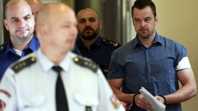 Petr Kramný v doprovodu eskorty na chodbě ostravského soudu.