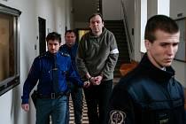 Eskorta přivádí k soudu Lumíra Heriče.
