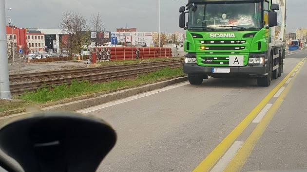 Popeláři v pruhu vyhrazeném MHD a IZS, podle mluvčí jejich firmy však mohou některá tato vozidla soužit ke svážení odpadu právě ze stavby ve Výškovické ulici.
