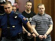 Vězeňská služba v úterý přivádí ke Krajskému soudu v Ostravě radikály Davida Vaculíka (vpravo) a Jaromíra Lukeše, kteří jsou s dalšími dvěma mladíky obžalováni ze žhářského útoku vůči romské rodině z Vítkova.