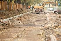 Staveniště. Místo chodníků se místní musí pohybovat po zemině, suti a kamení tvořící nerovnoměrný povrch.