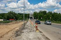 Stavba outletového centra v Ostravě, květen 2018. řípravné práce na dopravním připojení na Hlučínskou ulici. Chodník u silnice zmizel, místo něj bude jízdní pruh. Sloupy veřejného osvětlení čeká přeložení.