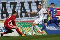 MARTIN ŠINDELÁŘ (v bílém), stoper ostravského Baníku, se snaží zabránit olomouckému Martinu Hálovi ve střetu s připraveným gólmanem Janem Laštůvkou.