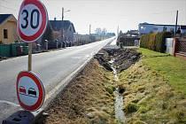 Pomezí dvou etap výstavby chodníku u Družební ulice v Ostravě-Krásném Poli, kde bylo nejprve potřeba zasypat hluboký příkop.