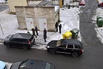 Porsche Cayenne - auto s modrým majákem na snímku u žluté popelnice.