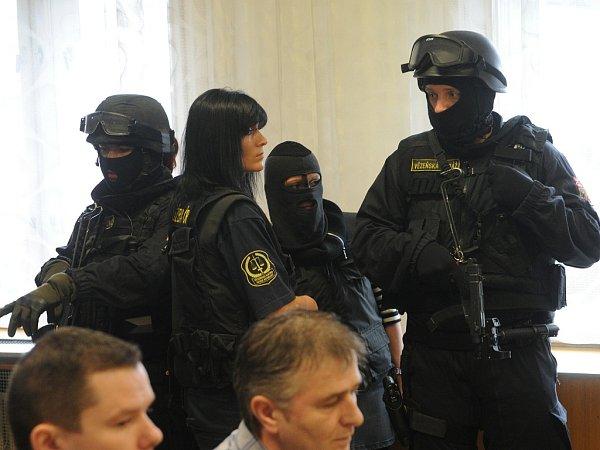 Ozbrojená eskorta chránila jednu zobžalovaných žen, která získala status spolupracující obviněné. Na sobě měla neprůstřelnou vestu a tvář jí zakrývala maska.