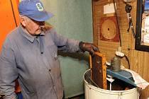 Šestaosmdesátiletý včelař Ivan Korba ze Slezské Ostravy při stáčení medu z druhé snůšky.