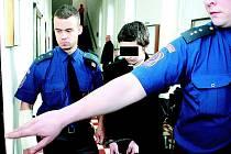 Vězeňská eskorta přivádí obžalovaného mladíka. Jeho tvář ukázat nemůžeme.