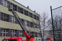 Odklízení sněhu ze střechy ZŠ Březinova v Ostravě-Hrabůvce.