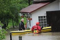 Z bílého domku číslo 147 v koblovském Žabníku paní Zdenka Burianová se svými dvěma psy tentokrát vyplula na hasičském člunu.