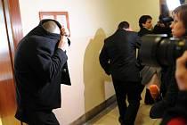 Někteří z obžalovaných si při odchodu z jednací síně kryli tvář.