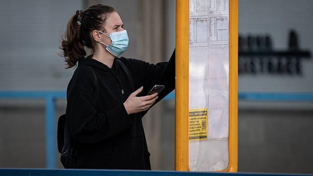 Žena s dvěma rouškami na zastávce MHD