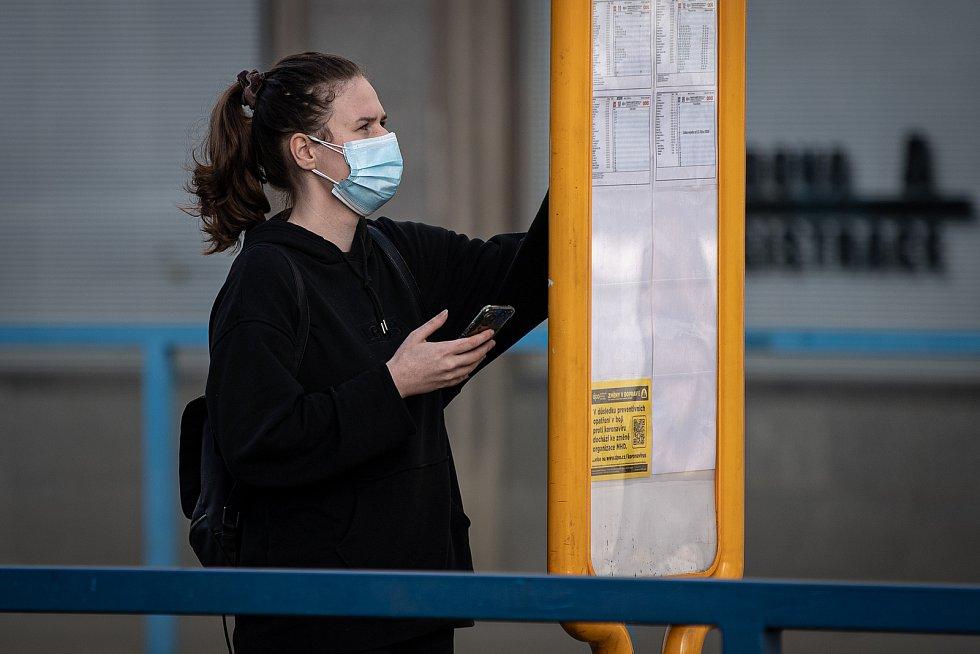 Žena s dvěma rouškami na zastávce MHD, 25. února 2021 v Ostravě. Kvůli koronavirové epidemii začala platit povinnost na frekventovaných místech nosit respirátor nebo dvě jednorázové zdravotnické roušky přes sebe.