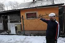 Jiří Koller ukazuje na dům romské rodiny v osadě Bedřiška v Ostravě-Hulvákách, do něhož v neděli nad ránem neznámý žhář údajně vhodil zápalnou láhev.