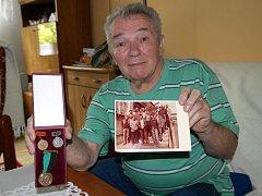 Vysloužilý havíř Zikmund Novák s pamětní medailí a snímkem své rubáňové osádky z Dolu Jan Šverma.
