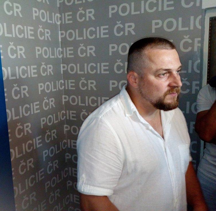 Policisté vedou na služebnu zadrženého mladíka.