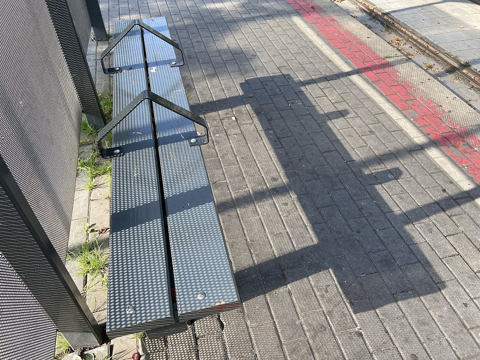 Rok 2020. Místo skleněných výplní perforovaný plech a lavičky s oblouky snižujícími kapacity.