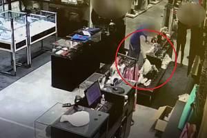 Zloděj vybírá věci z kabelky.