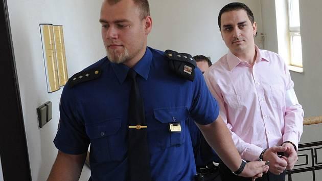 Eskorta přivádí obžalovaného Davida Dembinského do jednací síně.