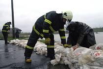 Desítky hasičů a vojáků budovaliv koblovské části Žabník hráz proti velké vodě