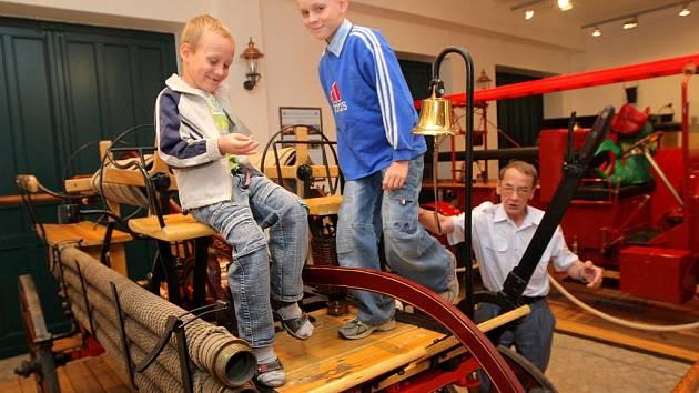 Marek Rylko z Ostravy (v modrém) se svým šestiletým bratrem Michalem a průvodcem Václavem Vašíčkem v hasičském muzeu.