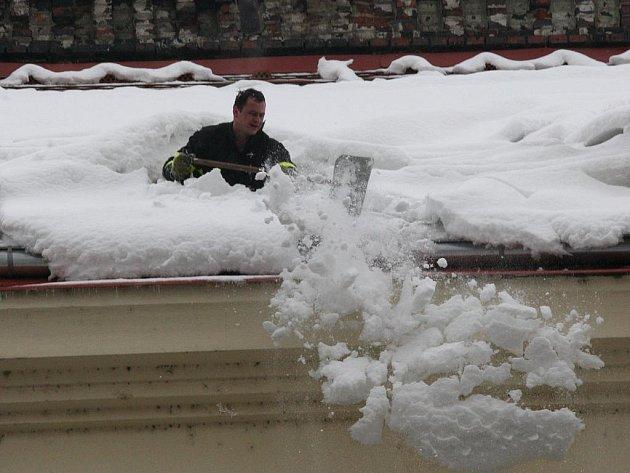Hasiči v pondělí po poledni shazovali hromady sněhu ze střechy domu v ostravské Nádražní ulici.