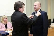 Bývalý starosta Karel Sibinský nasazuje starostovský řetěz svému nástupci. Tím byl ve čtvrtek odpoledne zvolen Martin Bednář (ANO).