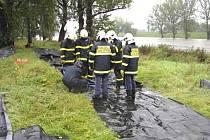Z ochraných vaků  naplněných vodou vytvoří hasiči hráz proti velké vodě