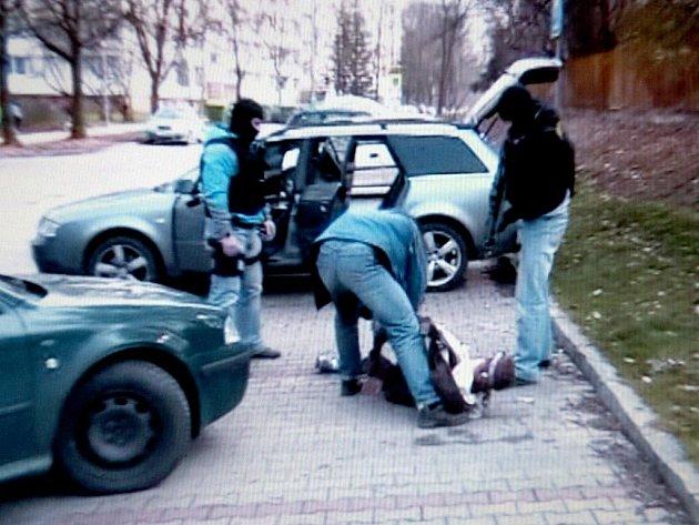 Fotografie je převzata z videozáznamu policie: Při razii policisté zadrželi i třináct narkomanů, kteří si v té době přebírali drogy.