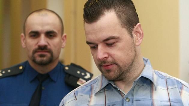 Petr Kramný v doprovodu eskorty na chodbě ostravského krajského soudu.