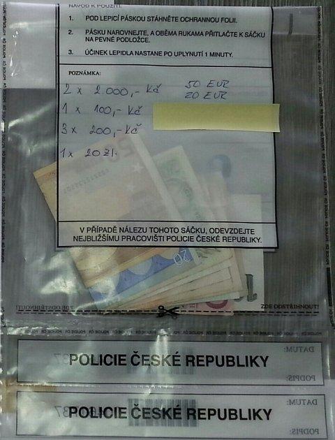 Policejní obálky se zajištěnými hotovostmi.
