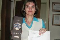 Veronika Klementová drží v rukou dárkové balení osmnáctileté whisky i se zápisem o jejím nálezu.