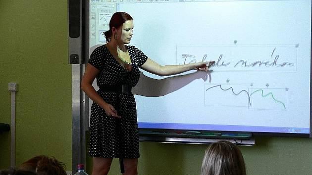 Lektorka vysvětluje práci s interaktivní tabulí učitelům školy ve Vrchlického ulici