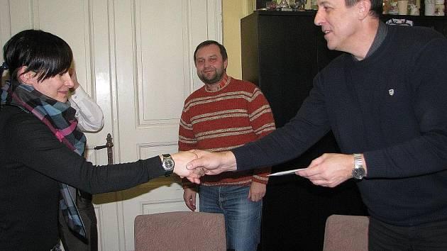 Věra Nedomová přebírá výtěžek prodejní akce od starosty Zdeňka Brože, vzadu je sleduje místostarosta Petr Suchomel