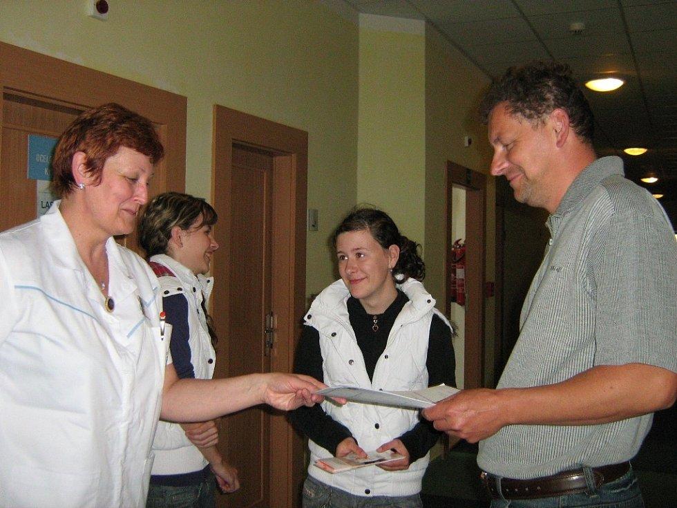 Návštěvníci kožní ambulance přebírají formuláře
