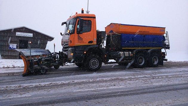 Sypače soukromé firmy Stavby, opravy a údržba silnic při zimní údržbě silnice na Červenohorském sedle.