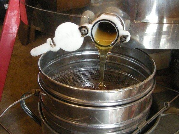 Med odtéká zhrnce a přes síta se čistí do nálevacího hrnce.