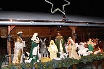 Obří nasvícený betlém s figurami vysokými až sto třicet centimetrů a s kometou nad nimi září do tmy před zahradnickým centrem u hlavní silnice v Rapotíně