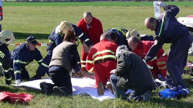 Záchranáři na šumperském letišti ošetřují těžce zraněného rogalistu.