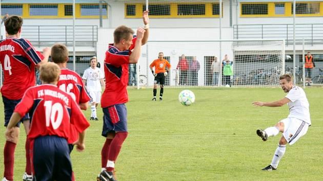 Prostějov (bílé dresy) v sobotním utkání s Mikulovicemi. Rozhodující střela zápasu – Petr Papoušek (vpravo) v nastavení posílá míč přes zeď Mikulovic a jeho střela se odráží od spojnice za brankovou čáru – 2:1.