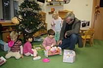 Děti z šumperského centra Pavučinka rozbalují dárky.