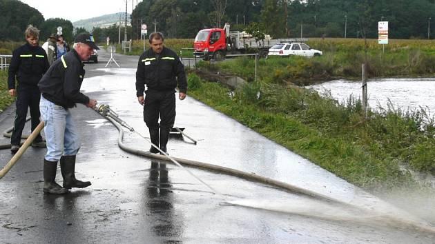 Sudkovští dobrovolní hasiči čistili včera silnici od bláta, které naplavila rozbouřená Desná.