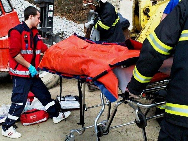 Záchranáři se snaži pomoci muži, kterého v Žulové zavalila radlice