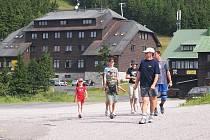 Turisté přecházejí silnici na Červenohorském sedle