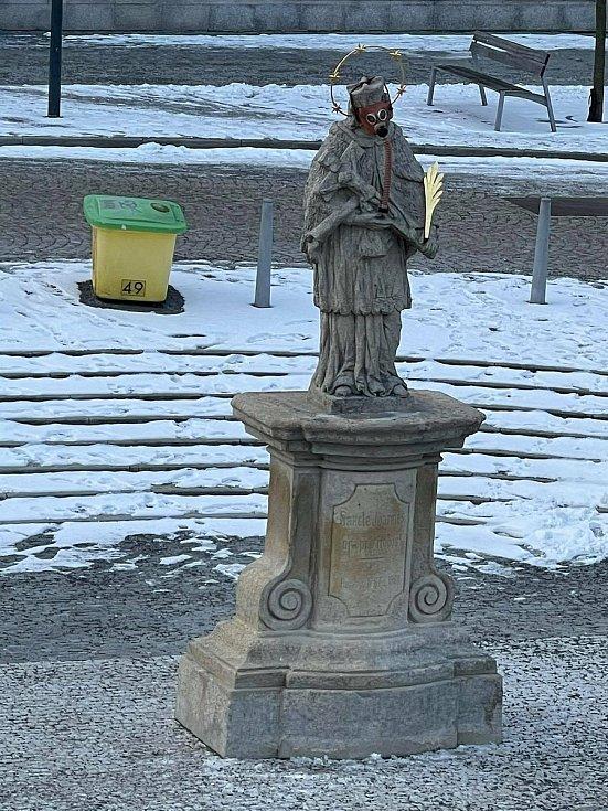 Socha svatého Jana Nepomuckého na náměstí v Jeseníku s plynovou maskou.
