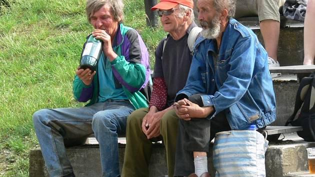 Bezdomovci s igelitkami, jejichž obsah zpravidla tvoří plastové láhve s vínem. Obrázek typický pro Sady 1. máje v Šumperku.